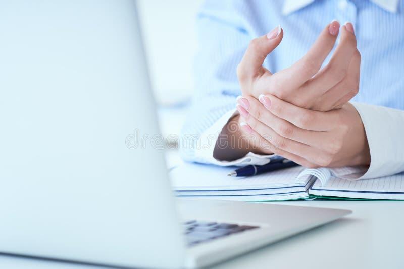 Młoda kobieta trzyma jej bolesnego nadgarstek w górę B?l od u?ywa? komputer Biurowy syndrom ręki ból okupacyjnym zdjęcia stock