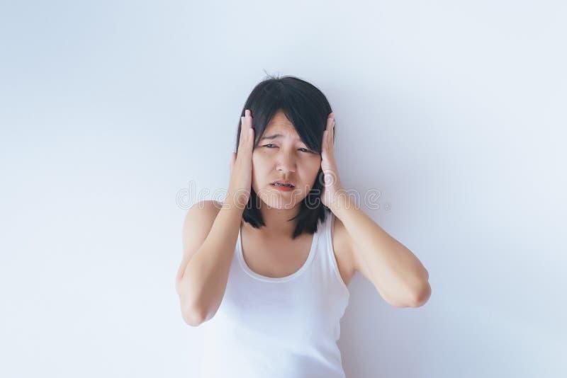 Młoda kobieta trzyma jej chorego ucho na białej tło ręce, Tinnitus obraz stock