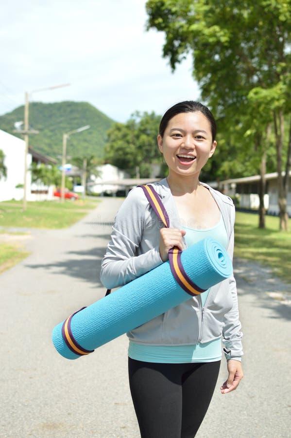 Młoda kobieta trzyma joga matę obraz stock