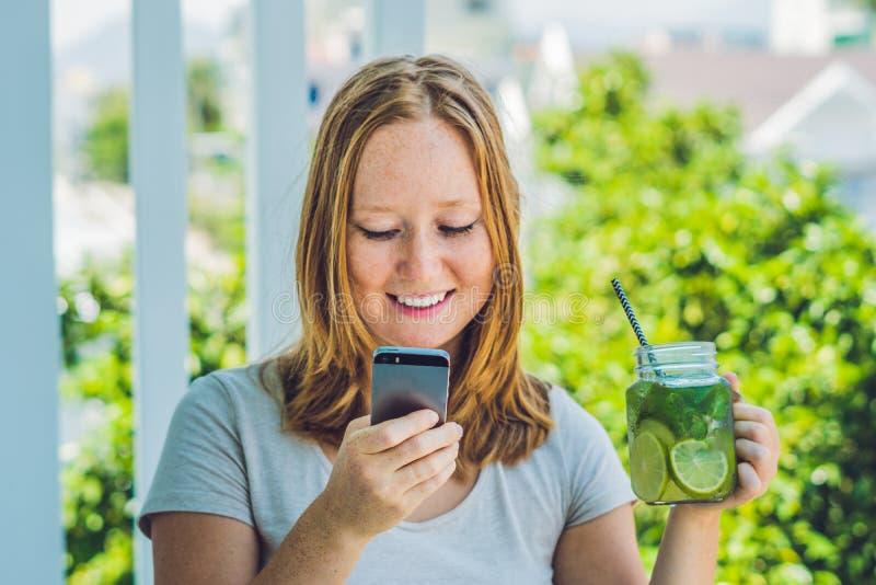 Młoda kobieta trzyma kamieniarza słój w jej ręce z mojito i smartphone Wiosna napoju pojęcie fotografia royalty free