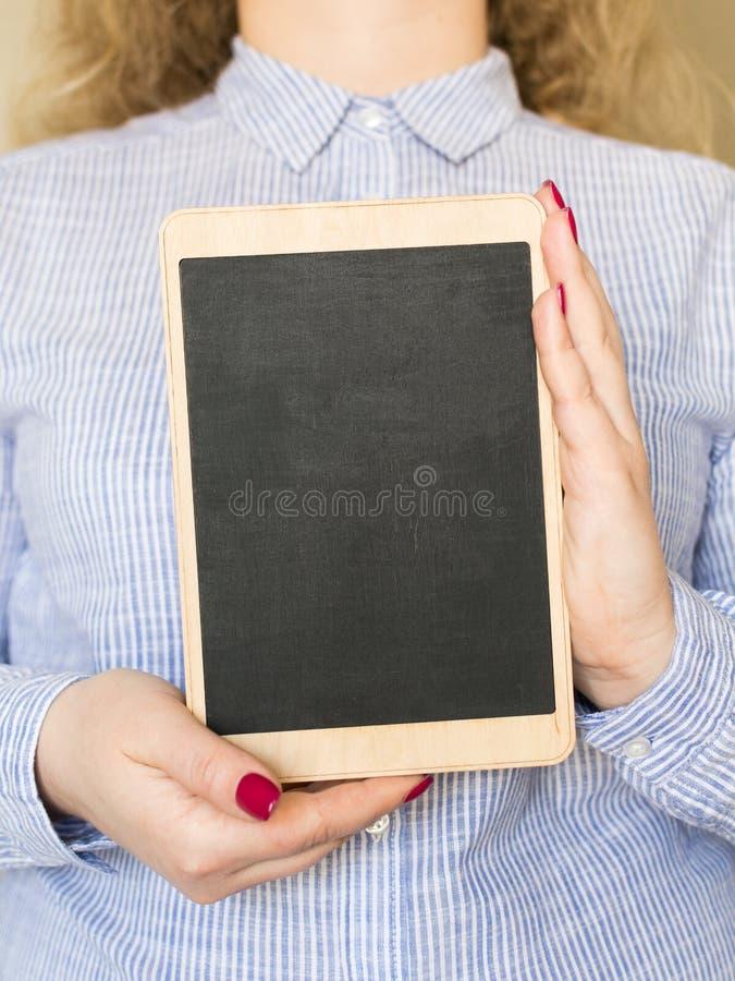 Młoda kobieta trzyma kredową deskę w ona ręki obrazy royalty free