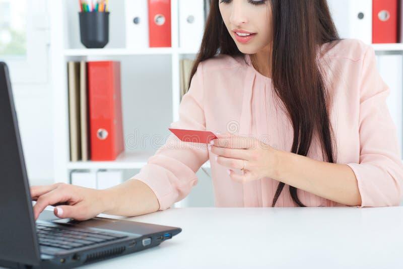 Młoda kobieta trzyma kredytową kartę w ręce i wchodzić do ochrona kod używać laptop klawiaturę obrazy stock