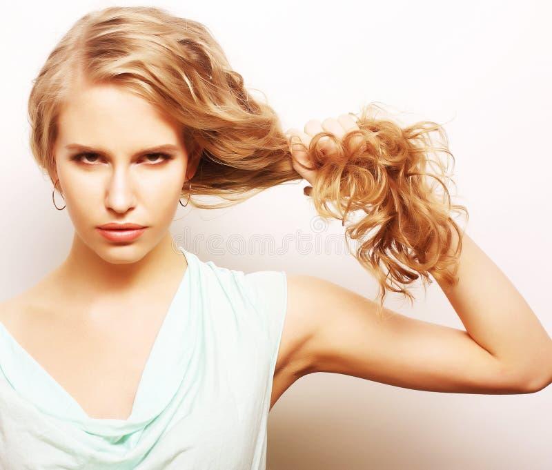 Młoda kobieta trzyma ona długo kędzierzawy zdrowy włosy obraz stock