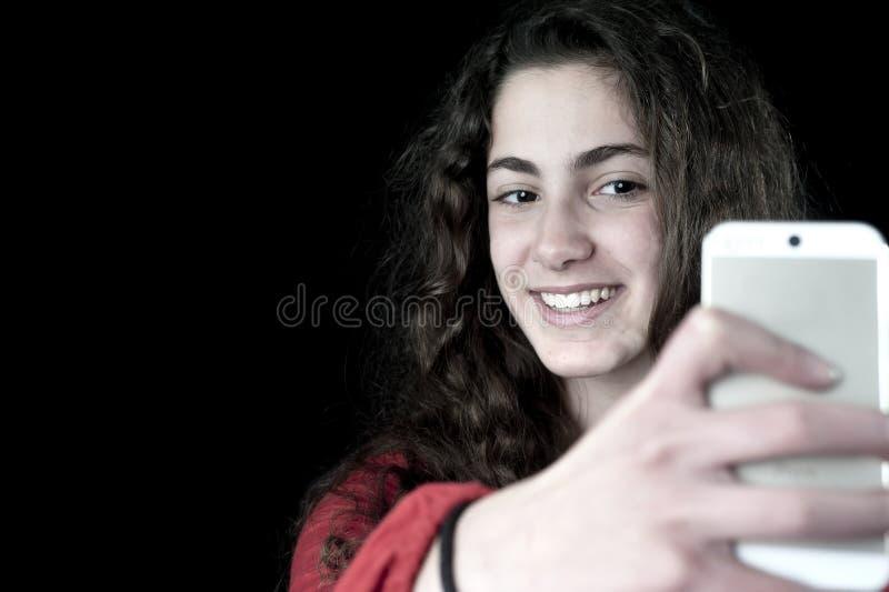 Młoda kobieta trzyma smartphone zdjęcia stock