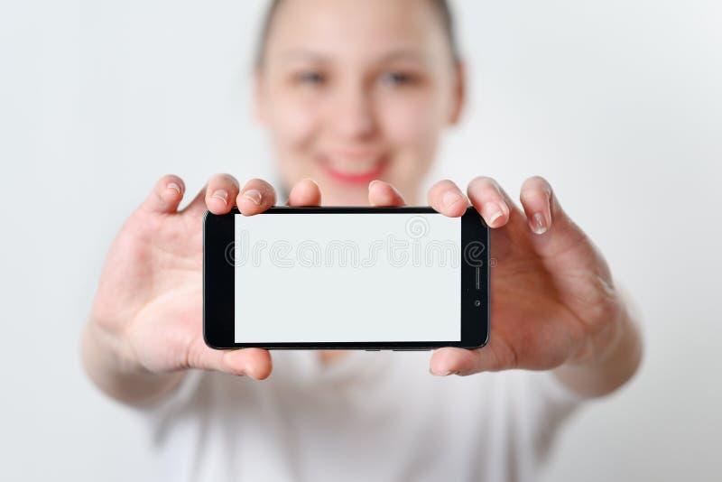 Młoda kobieta trzyma smartphone horizontally z białym ekranem z miejscem dla copyspace na lekkim tle obrazy stock