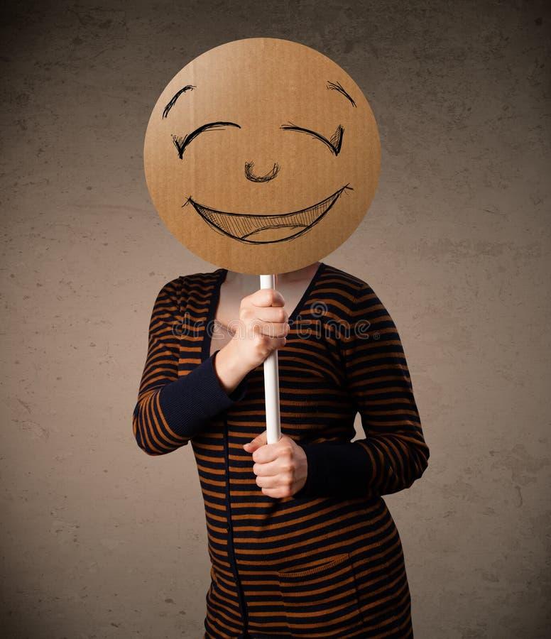 Młoda kobieta trzyma smiley twarzy deskę zdjęcia stock