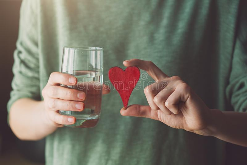 Młoda kobieta trzyma szkło woda i czerwony drewniany serce zdjęcia stock