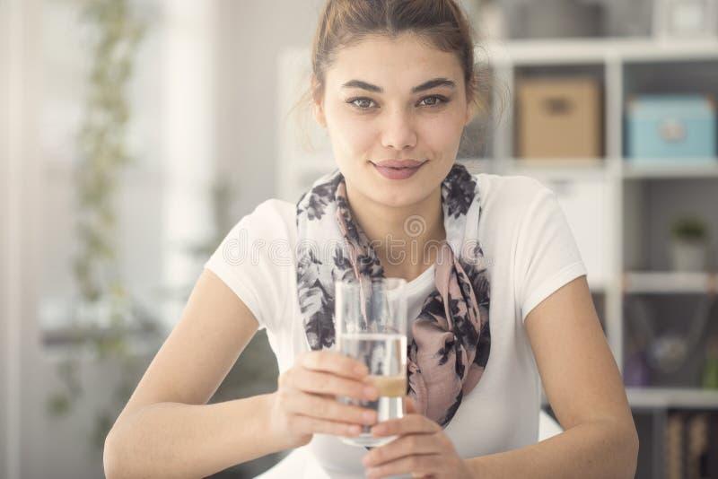 Młoda kobieta trzyma szkło woda w kuchni zdjęcie stock