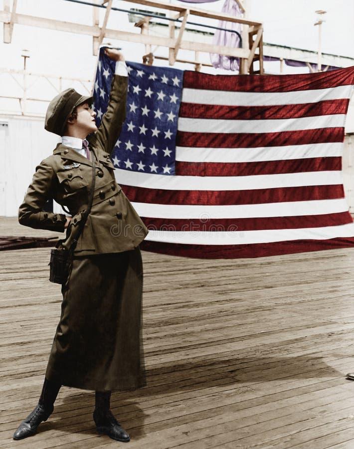 Młoda kobieta trzyma up flaga amerykańską w wojskowym uniformu (Wszystkie persons przedstawiający no są długiego utrzymania i żad fotografia royalty free