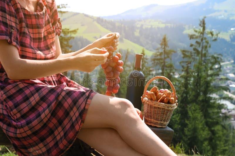 Młoda kobieta trzyma wiązkę winogrona przeciw góra krajobrazowi obraz stock