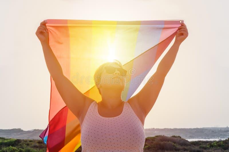 Młoda kobieta trzyma z nastroszonymi rękami macha LGBT homoseksualną tęczę w okularach przeciwsłonecznych zaznacza zdjęcie royalty free