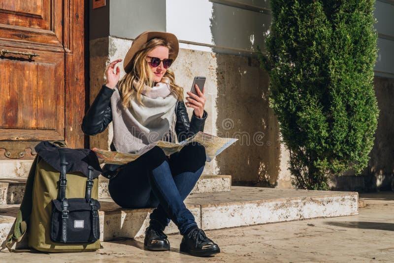 Młoda kobieta turysta siedzi na ulicie na krokach, patrzeje dla ścieżki na mapie, obok jej plecaka Turystyka, podróż, wakacje zdjęcia stock
