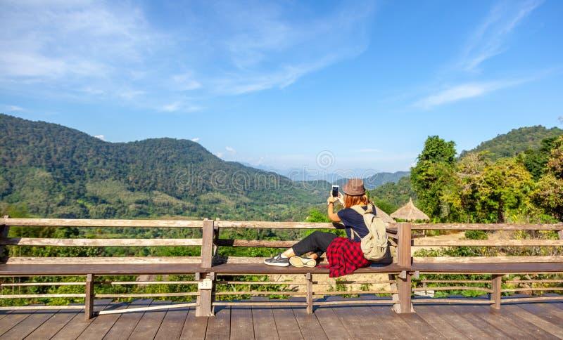 Młoda kobieta turysta z plecakiem w kapeluszu podziwia widok w górach Laos, popularny podróży miejsce przeznaczenia w południowyc zdjęcia royalty free