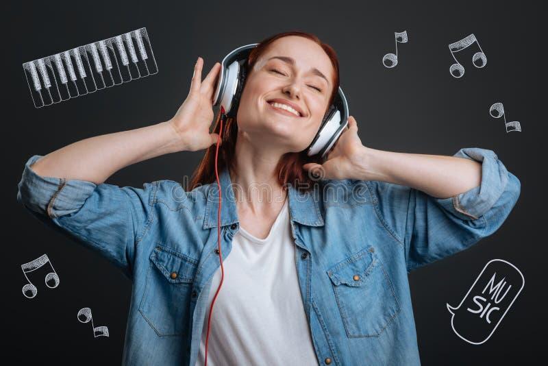 Młoda kobieta uśmiecha się ona i zamyka oczy podczas gdy słuchający muzyka obrazy stock