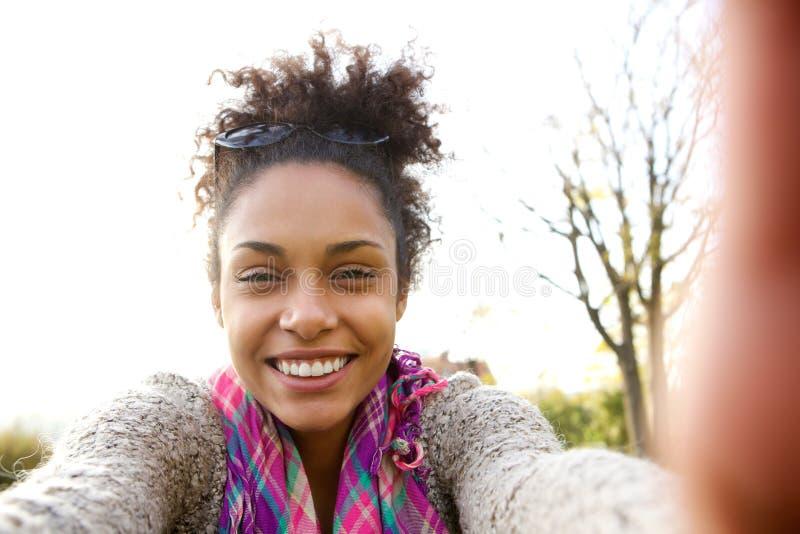 Młoda kobieta uśmiecha się selfie i opowiada fotografia stock