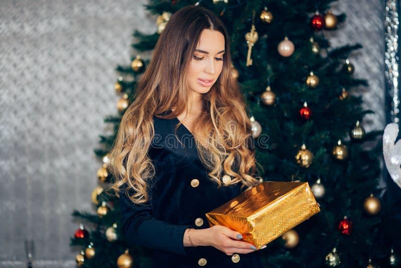 Młoda kobieta uśmiechu chwyta prezenta szczęśliwy pudełko w rękach zbliża choinki obrazy royalty free