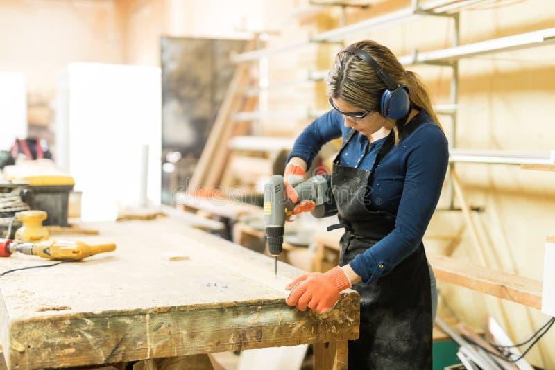 Młoda kobieta używa śrubokręt przy pracą zdjęcia stock