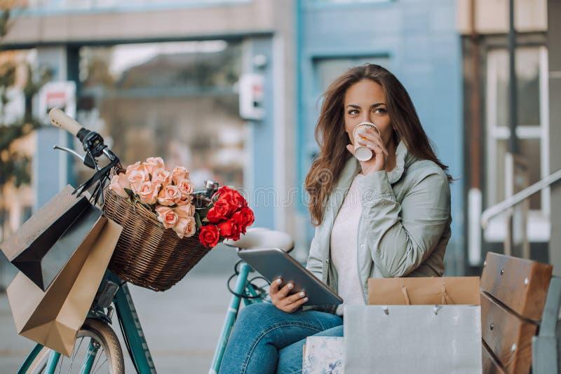Młoda kobieta używa cyfrową pastylkę i pijący caffee obraz royalty free