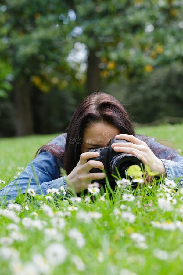 Młoda kobieta używa dslr plenerowy kłaść na trawie fotografia stock