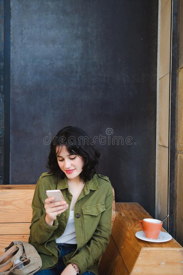 Młoda kobieta używa jej telefon komórkowego podczas gdy mieć kawę zdjęcie royalty free