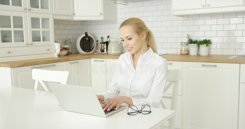 Młoda kobieta używa laptop przy kuchnią fotografia royalty free