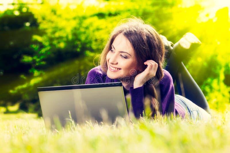 Młoda kobieta używa laptop w parkowym lying on the beach na zielonej trawie fotografia stock