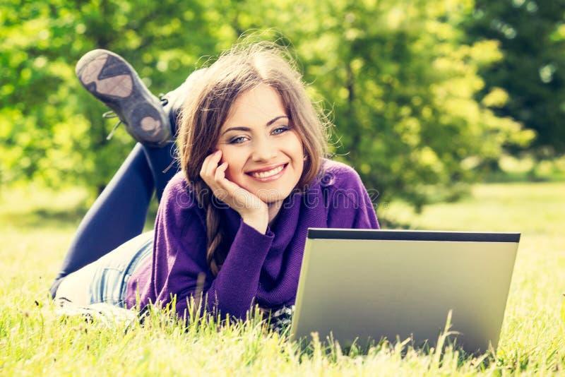 Młoda kobieta używa laptop w parkowym lying on the beach na zielonej trawie obraz royalty free
