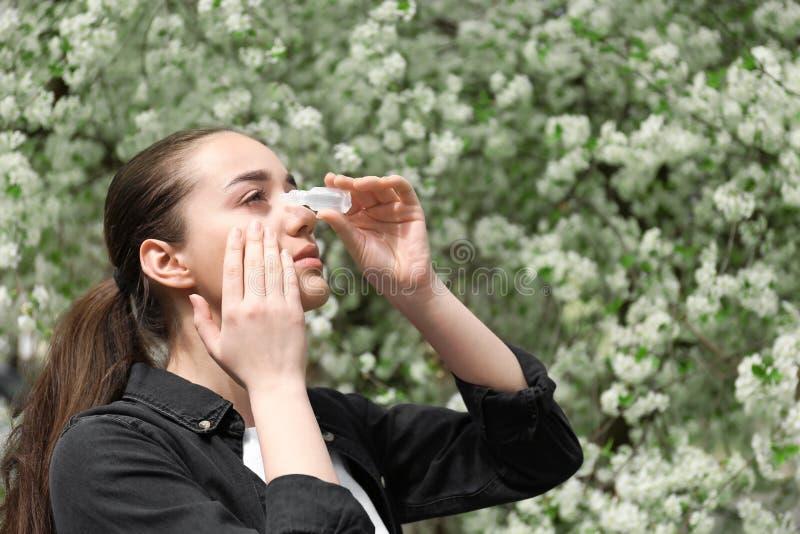 Młoda kobieta używa oko krople zbliża kwitnącego drzewa Alergii poj?cie obrazy royalty free