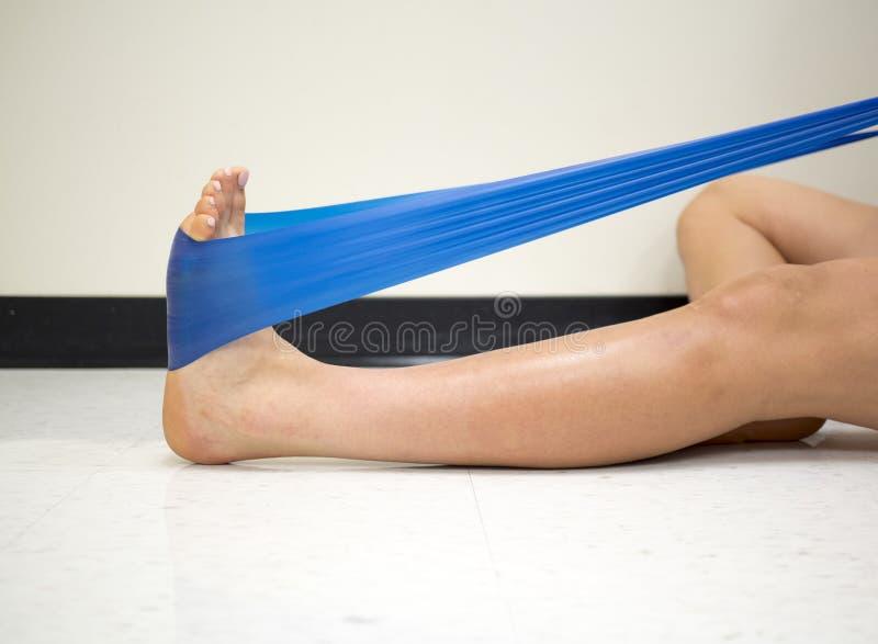 Młoda kobieta używa oporu zespołu dla kostki ćwiczy w gym zdjęcia royalty free