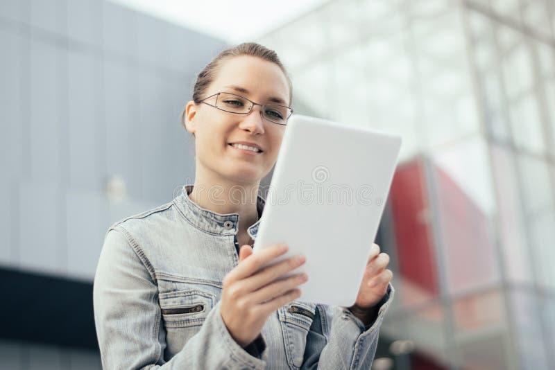 Młoda kobieta używa pastylki komputerowy plenerowego w mieście zdjęcia royalty free