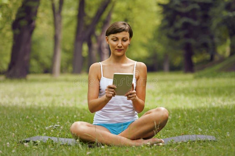 Młoda kobieta używa pastylki plenerowy być usytuowanym na trawie, ono uśmiecha się obraz royalty free