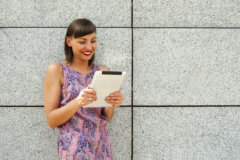 Download Młoda Kobieta Używa Pastylki Pozycję Przeciw ścianie W Mieście Zdjęcie Stock - Obraz złożonej z ulica, kobieta: 57659376