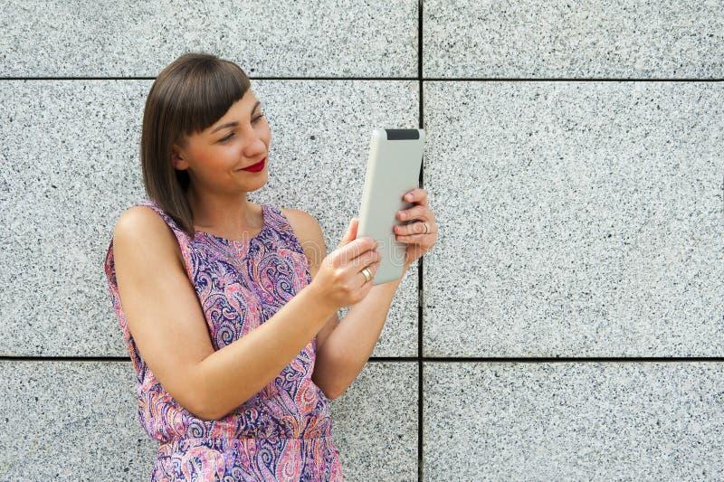 Download Młoda Kobieta Używa Pastylki Pozycję Przeciw ścianie W Mieście S Zdjęcie Stock - Obraz złożonej z femaleness, uśmiech: 57659550