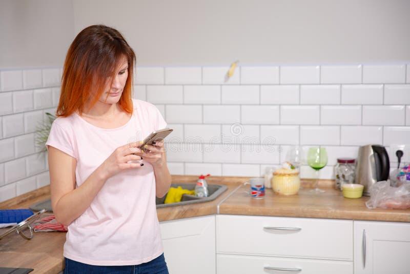Młoda kobieta używa smartphone opiera przy kuchnią w nowożytnym domu kobieta telefonu czytelnicza wiadomość rudzielec kobieta pis fotografia royalty free
