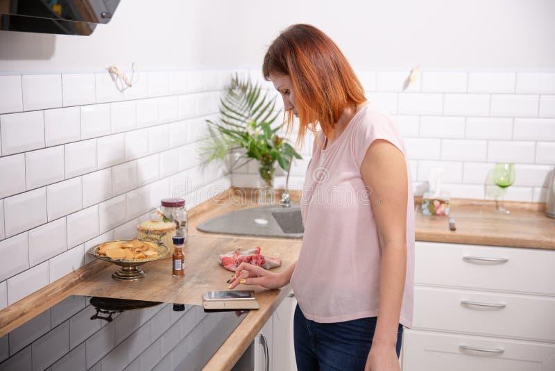 Młoda kobieta używa smartphone opiera przy kuchnią w nowożytnym domu kobieta telefonu czytelnicza wiadomość rudzielec kobieta pis zdjęcie royalty free