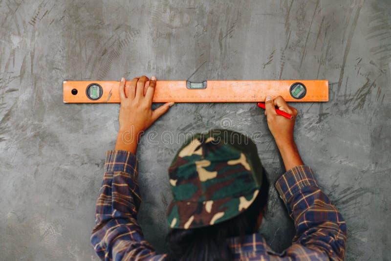 Młoda kobieta używa spirytusowego poziom i zaznaczający ścianę z piórem obraz royalty free