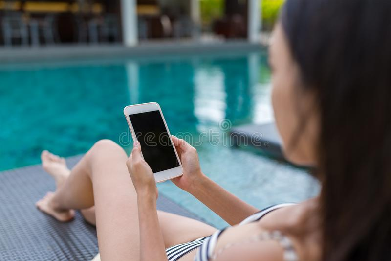 Młoda Kobieta używa telefon komórkowego i lying on the beach oprócz pływackiego basenu fotografia stock