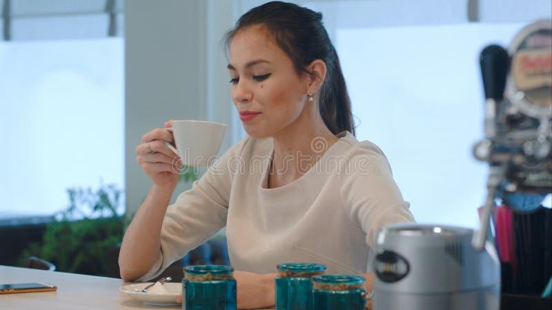 Młoda kobieta używa telefon przy kontuarem podczas gdy czekający kawę fotografia royalty free