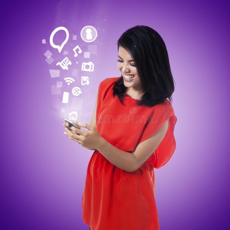 Młoda kobieta używa wiszącą ozdobę app obrazy royalty free