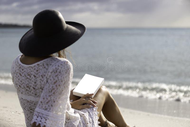 Młoda kobieta ubierał w białej koronki sukni, białej bieliźnie za i dużym czarnym kapeluszu od obsiadania, dennym mieniem książka zdjęcia royalty free