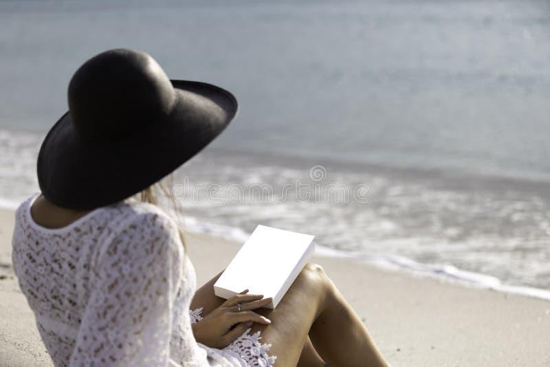 Młoda kobieta ubierał w białej koronki sukni, białej bieliźnie za i dużym czarnym kapeluszu od obsiadania, dennym mieniem książka zdjęcie stock