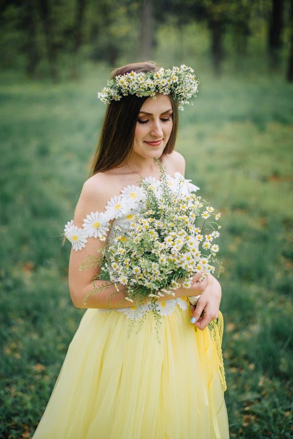 Młoda kobieta ubierał w pięknej delikatnej sukni i wianku stokrotki zdjęcia royalty free