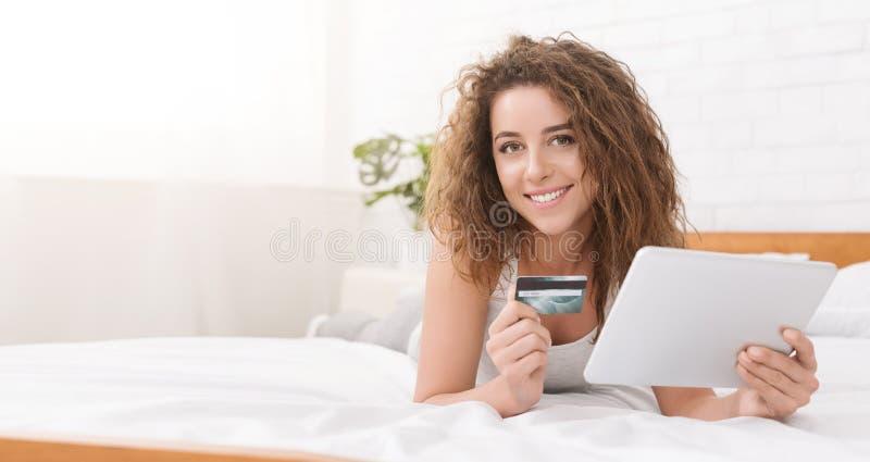 Młoda kobieta w łóżku robi online zakupy z cyfrową pastylką zdjęcie stock