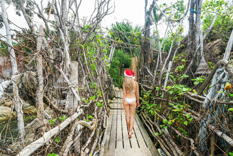 Młoda Kobieta w Święty Mikołaj Kapeluszowym spacerze przez Autentycznego Drewnianego most Odświętność nowy rok w gorącym kraju obraz royalty free