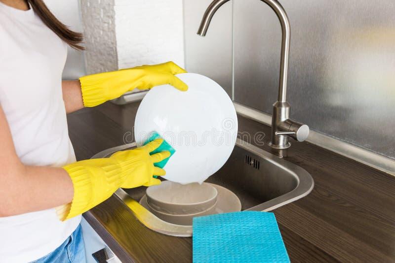 Młoda kobieta w żółtych rękawiczkach myje naczynia z gąbką w zlew Domowego profesjonalisty czy?ci us?uga zdjęcie royalty free