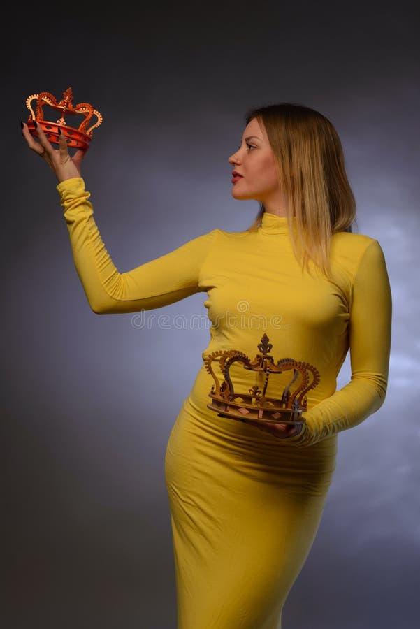 Młoda kobieta w żółtych wieczór sukni chwytach w rękach dwa korony fotografia royalty free