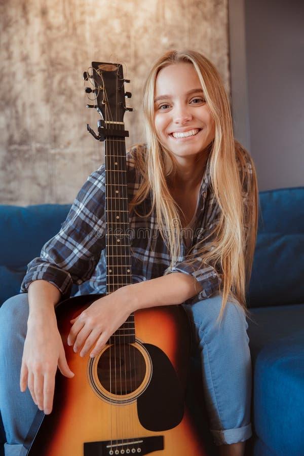 Młoda kobieta w żywym pokoju z gitarą w domu zdjęcie royalty free