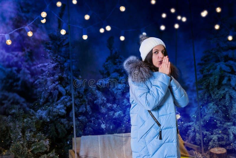 Młoda kobieta w błękita puszka kurtki nagrzania rękach blisko i pozyci zdjęcia stock