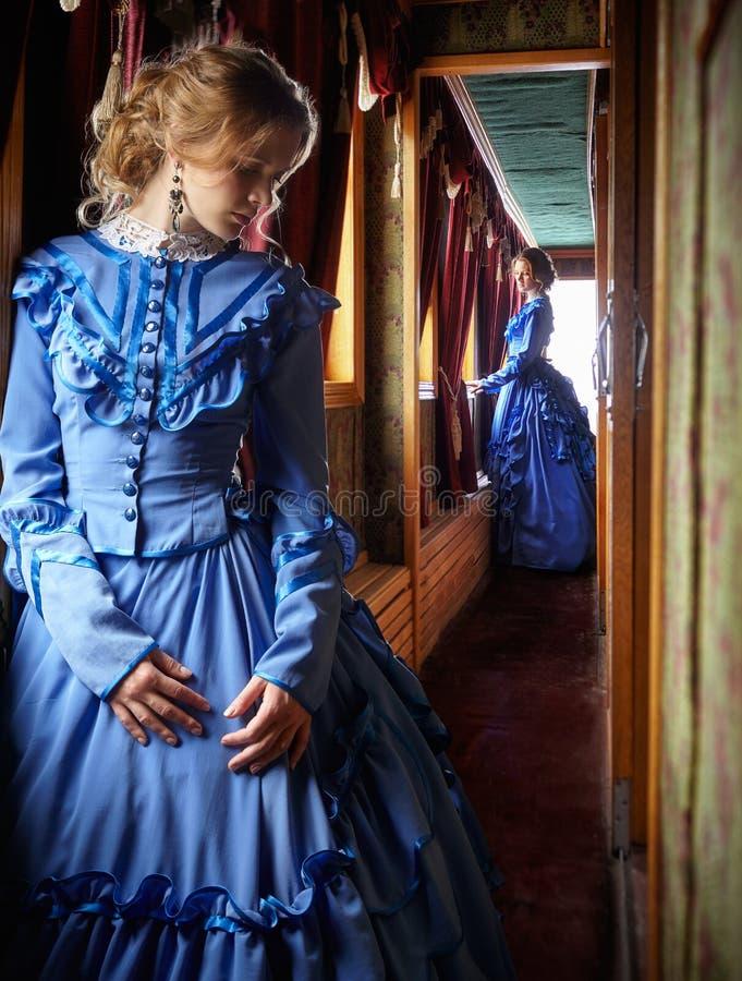Młoda kobieta w błękitnej rocznik sukni pozyci w korytarzu retro