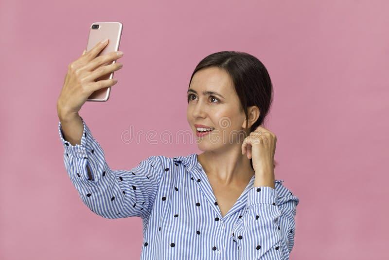 Młoda kobieta w błękitny koszulowym mieć zabawę z robić selfie Studio strzał przeciw różowemu tłu obrazy royalty free